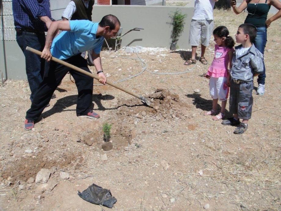 Ehab planting his cedar sapling