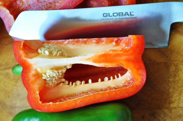 A knife cutting into a pepper