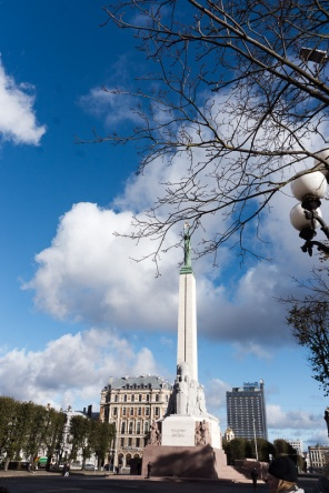 Blue sky with fluffy clouds and the Freedom monument in the centre of a square