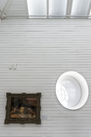 A painting on a wooden wall next to an oval window