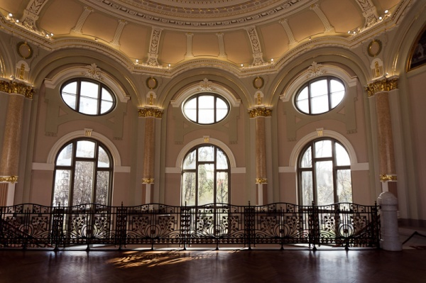 Curved Regency style windows and a balcony inside the second floor of the art gallery