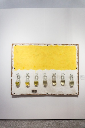Painting of a yellow stripe with bottles below