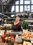 A lady smiling behind a fruit and veg stall