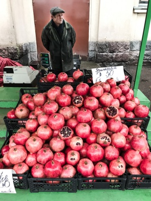Man behind stall of pomegranates