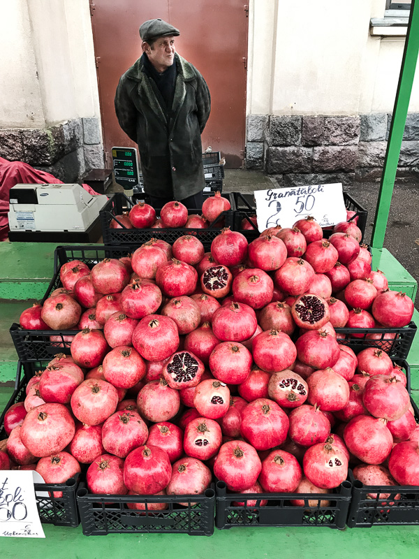 Man behind stall of pomegranates
