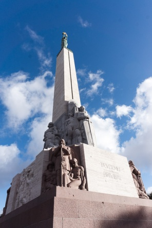 Looking up at tall statue with blue sky and clouds, the Freedom monument Riga