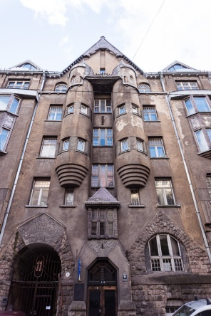 brown house with a pointed roof and barrel shaped columns in riga latvia