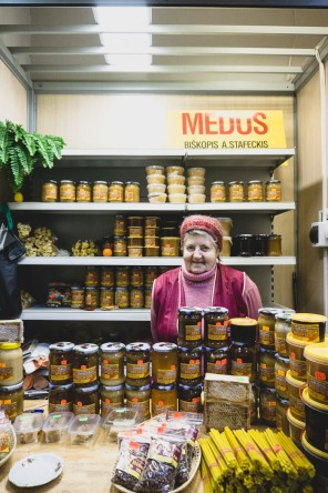Lady in front of jars of honey at market in Riga