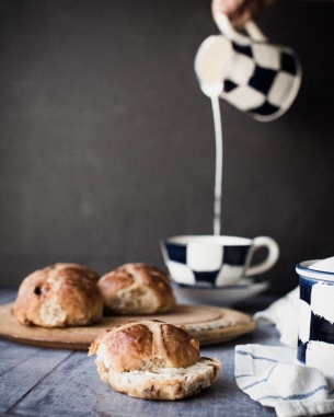 milk pouring from jug into a tea cup and hot cross buns