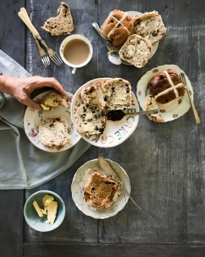 hot cross buns on plates with a cup of tea