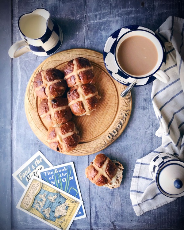hot cross buns on a board with a cup of tea