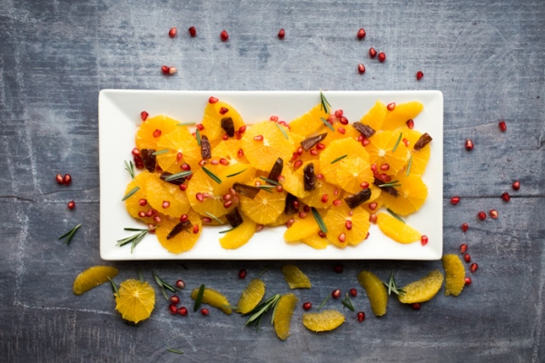 Date and orange fruit salad on a plate with segments scattered around