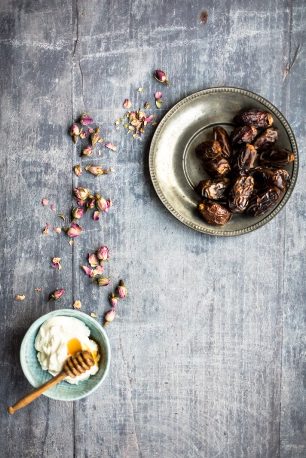 A bowl of dates, some rose buds and yoghurt with a honey drizzler