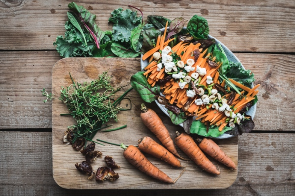 A chopping board with carrots, herbs, dates and a plate of date and carrot salad
