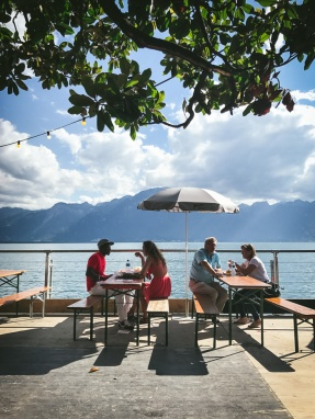 people sitting at tables by lake geneva