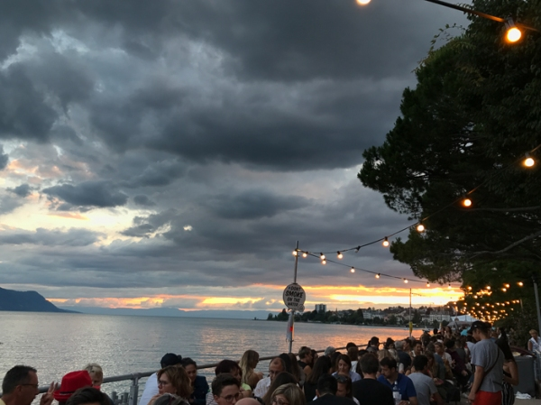 sunset over lake geneva with people and fairy lights