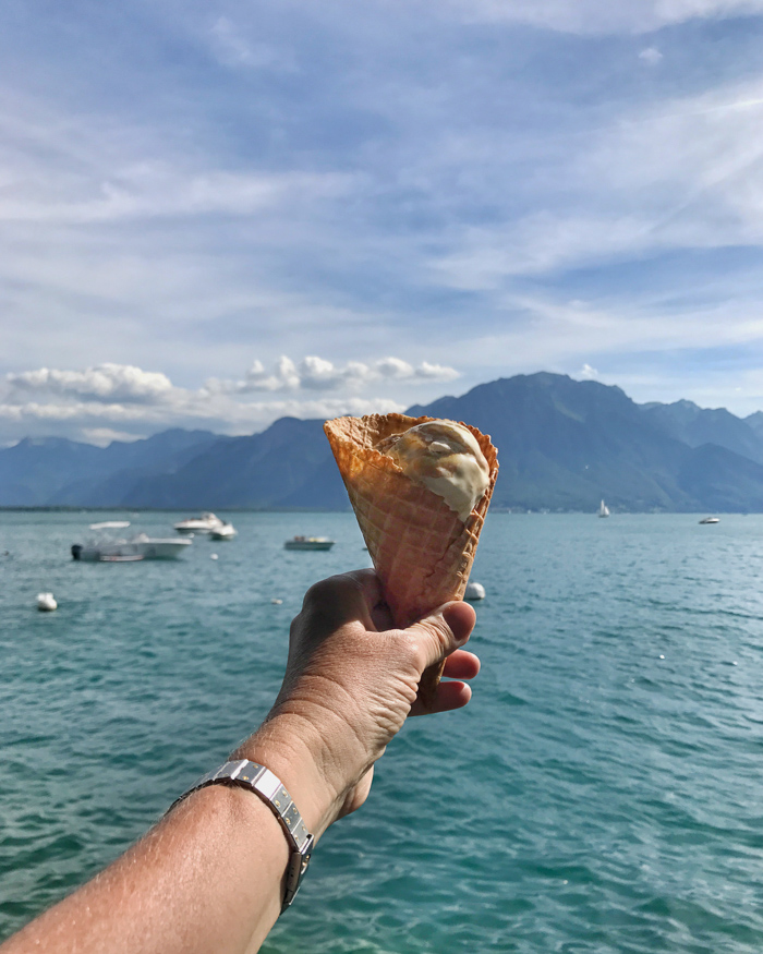 Hand with ice cream in front of lake
