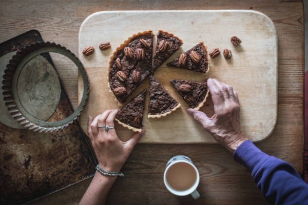 hands reaching in for slices of mock pecan pie