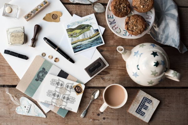 Pens, paper and notebooks for writing a newsletter plus teapot, tea and muffins
