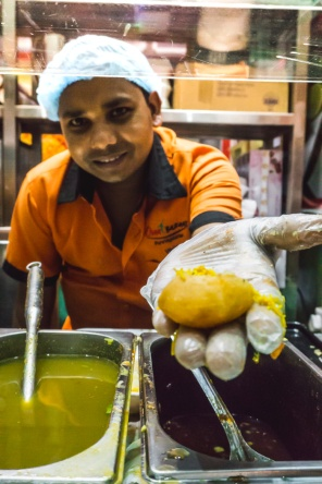 pani puri in a chaat man's hand