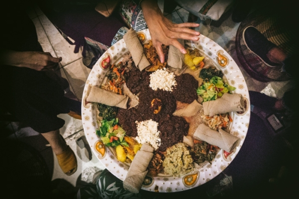 people eating a big platter of Ethiopian food with their hands