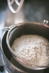 flour in a seive for gingerbread making