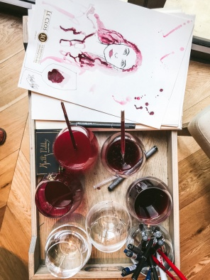 wine with paint brushes and a portrait in wine