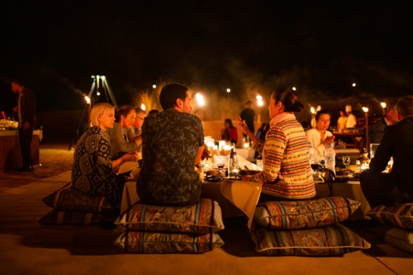 people sitting around a dining table on cushions in the desert at night