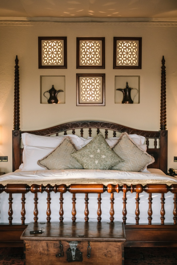 a wooden king sized bed with alcoves and coffee pots