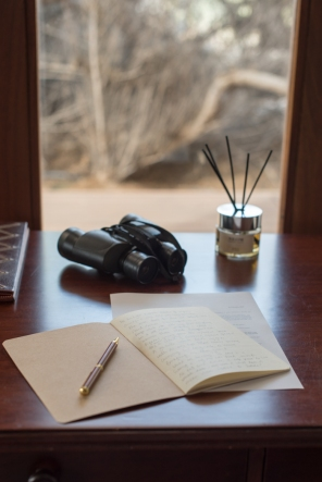 binoculars and writing materials on desk