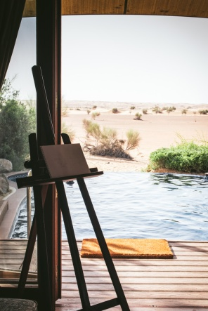 easel with with of swimming pool and desert