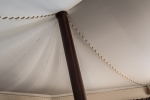 tented roof with stitched seams supported by a wooden pole