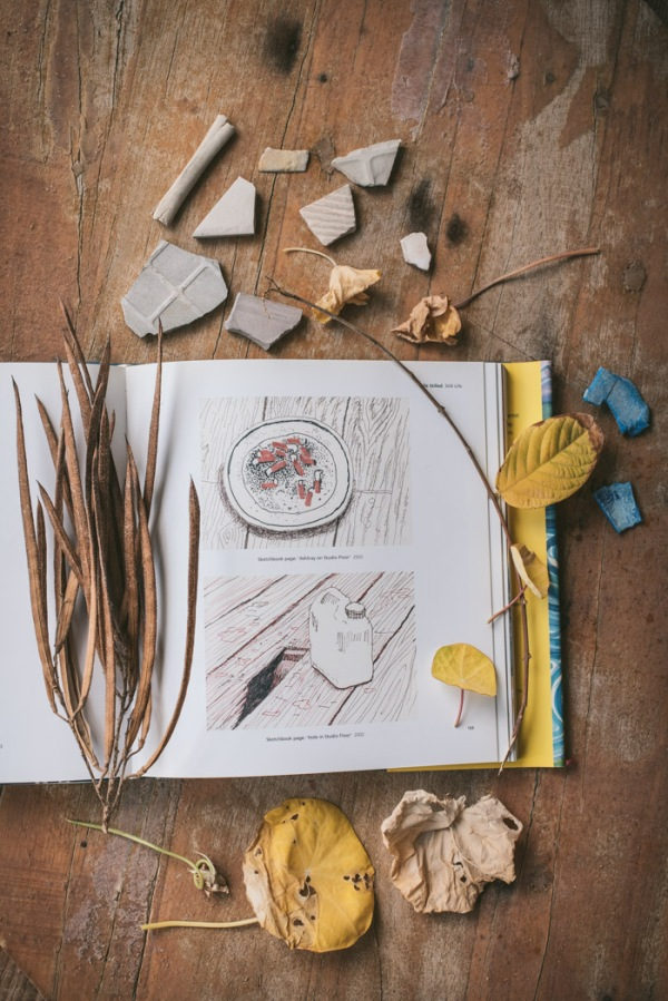 a book of David Hockney art surrounded by leaves and other bits and pieces