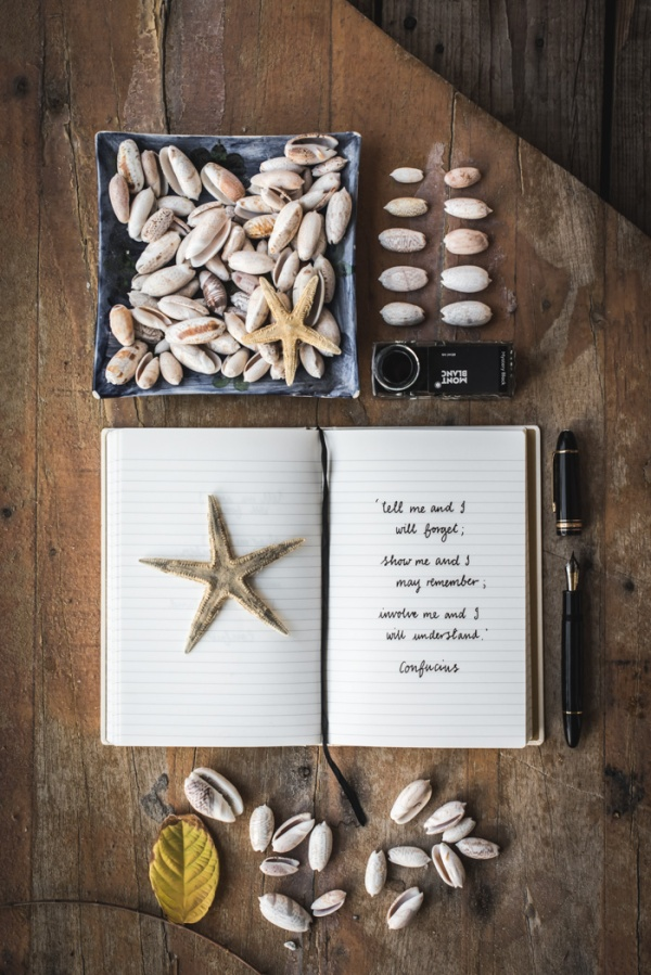 a book open to a quote by confucias, shells, a star fish, a mont blanc pen