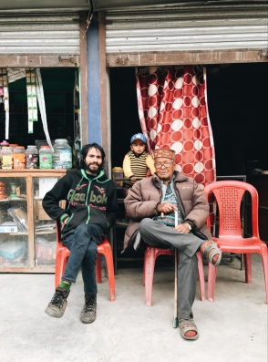 two men and a boy sitting on chairs in front of a shop