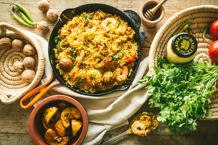 skillet with rice and honey mustard prawns with ingredients coriander and loumi