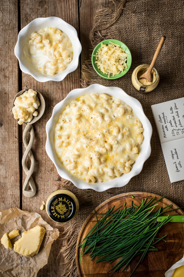 Two bowls of mustard macaroni cheese with a serving spoon