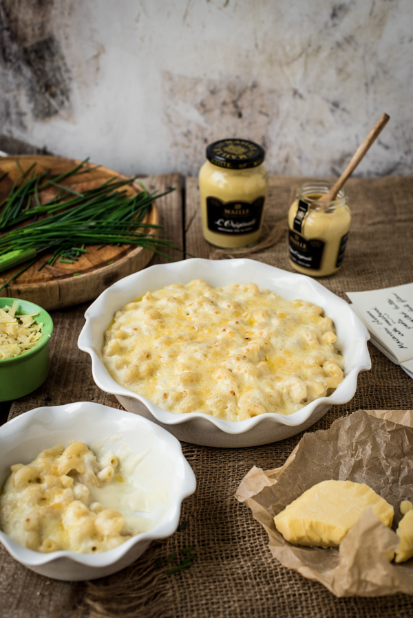 Two bowls of mustard macaroni cheese with two jars of Maille mustard