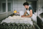 shaping the curds into the moulds by hand