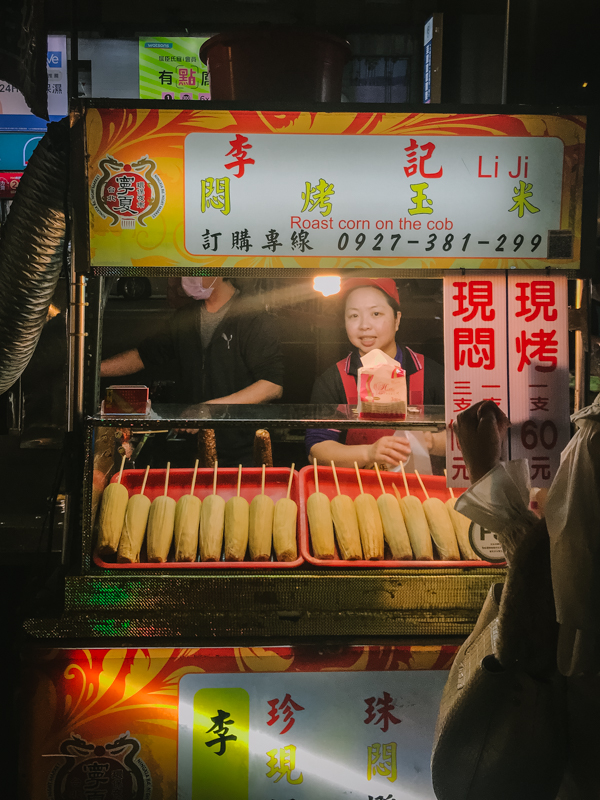 corn cobs on sticks at a stall