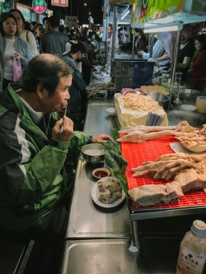 man eating at stall