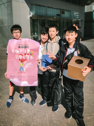 four boys carrying a box
