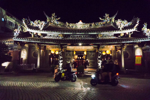Motorbikes driving past the Baoan temple