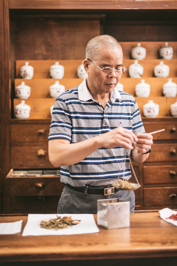 man weighing out chinese medicine