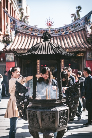girls burning incense outside a temple
