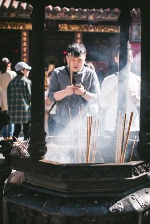 man offering a prayer by incense burner