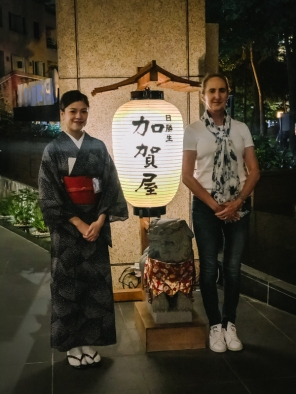 two women standing by Chinese lamp