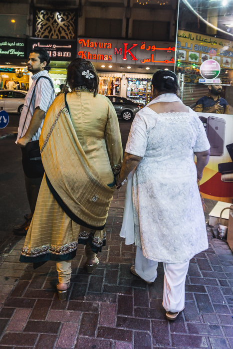 ladies in saris holding hands
