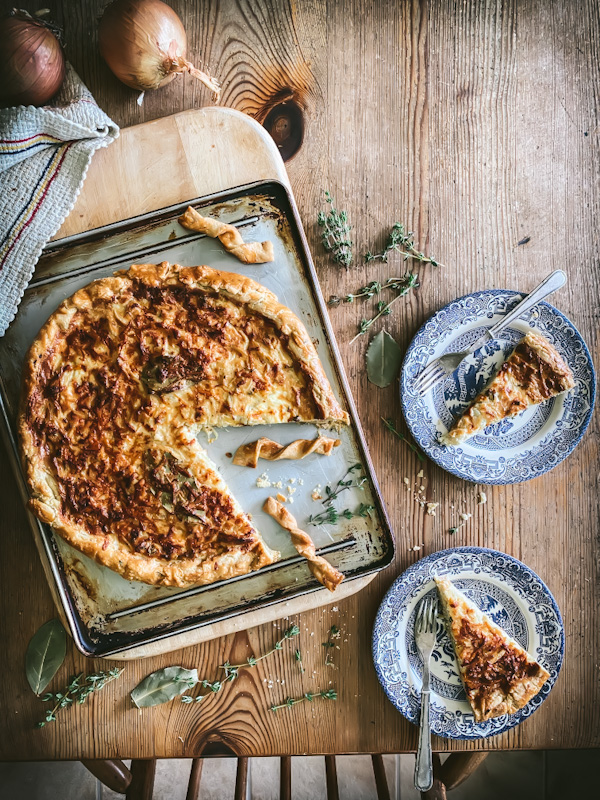 onion and thyme tart with slices on plates